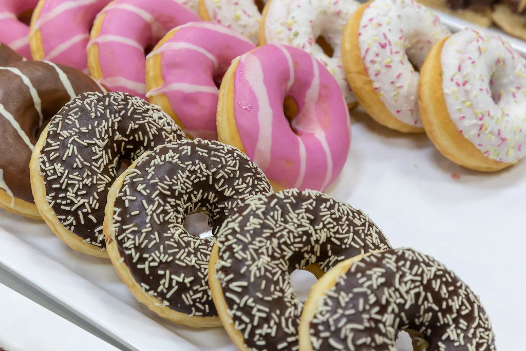 Donuts with different toppings, with dark chocolate, pink and white icing and patterns on white tray