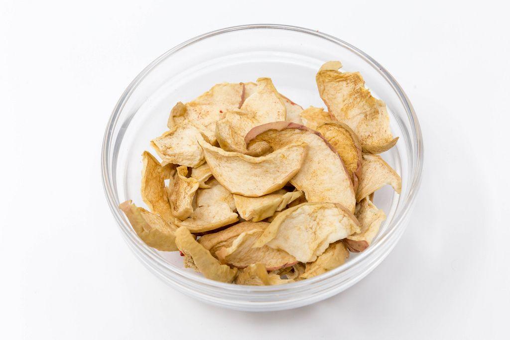 Dörrwerk - Getrocknete Apfel Chips mit Zimt in Glaschale auf weißem Hintergrund