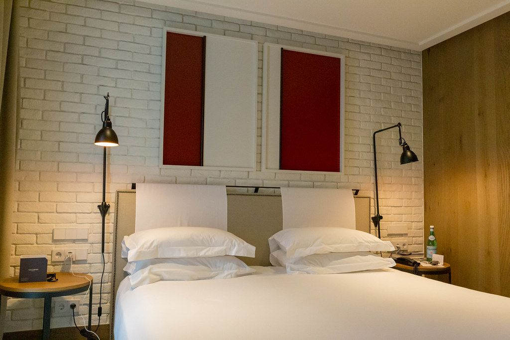 Double bed with white sheets and brick wall in the hotel room of