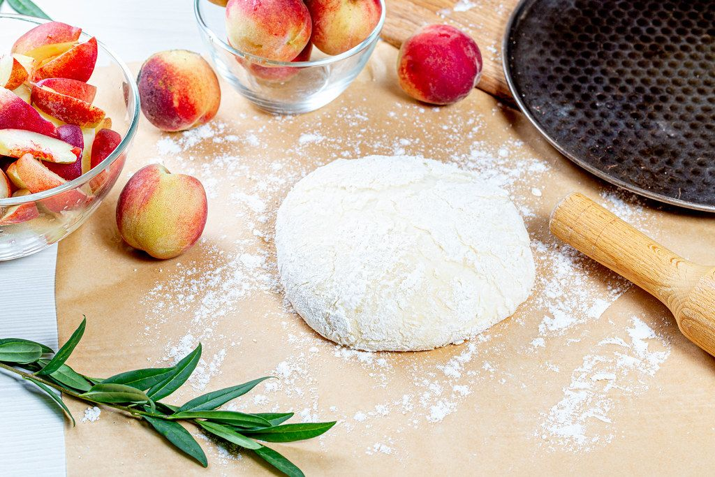 Dough, flour and fresh peaches with rolling pin and baking sheet on the table