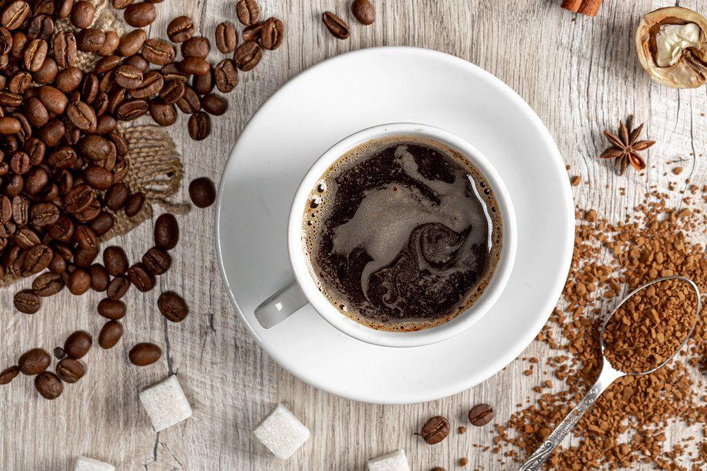 Draufsicht - eine Tasse heißer Kaffee mit ganzen und gemahlenen Kaffeebohnen, Zucker und Gewürzen auf einem Holzhintergrund