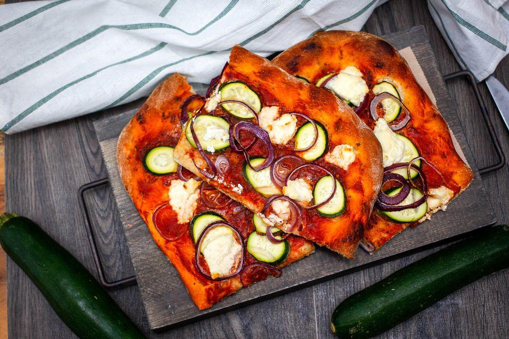 Draufsicht einer vegetarischen Pizza mit Zucchini und roten Zwiebeln