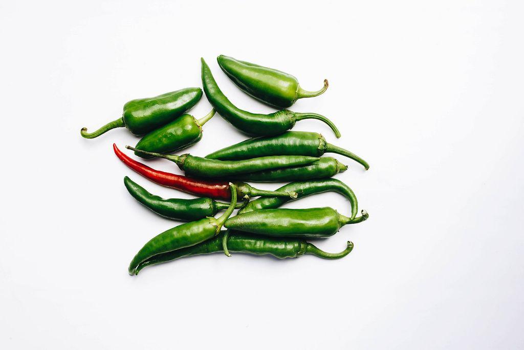 Draufsicht von grünen und roten Chilischoten vor weißem Hintergrund
