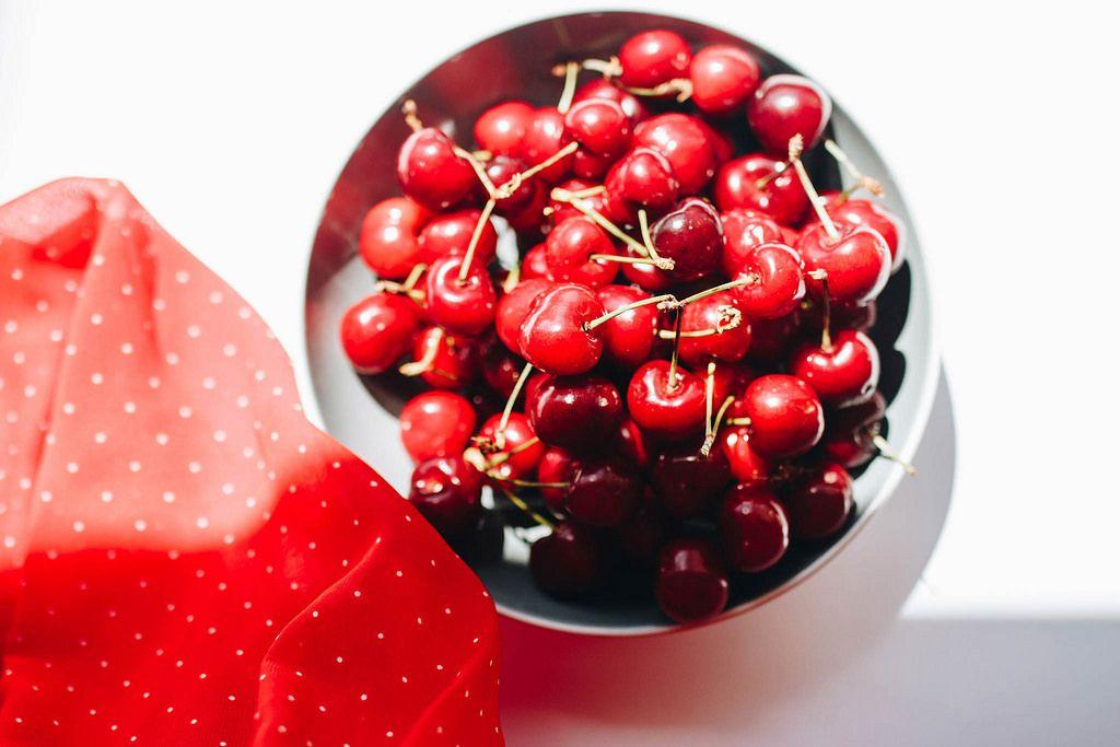 Draufsicht von Kirschen in einer Schüssel und rotem Stoff