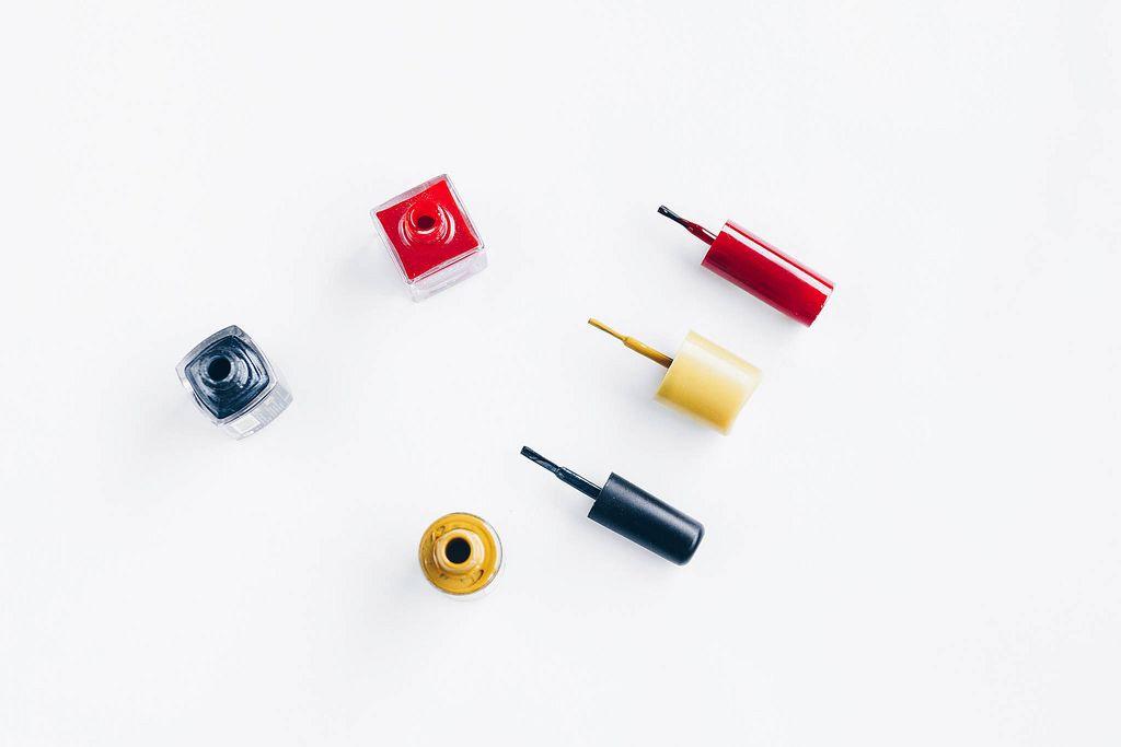 Draufsicht von Nagellack in verschiedenen Farben vor weißem Hintergrund