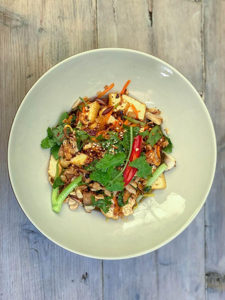 Draufsicht von PHO XAO SOT ME. Bio-tofu in Streifen gebraten mit Bandnudeln, Zwiebeln, Möhren, Buschbohnen, Shiitake-pilzen, Tamarindesauce, Sesam, Erdnüsse, Röstzwiebeln