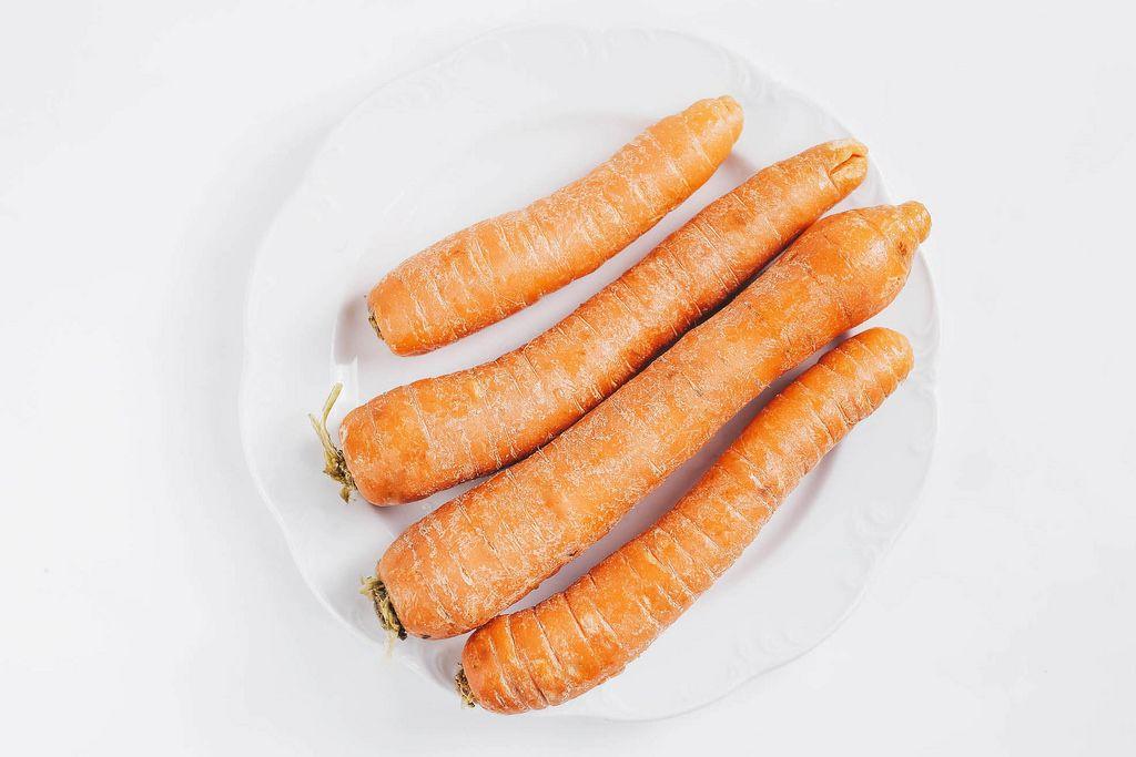 Draufsicht von ungeschälten Karotten vor weißem Hintergrund