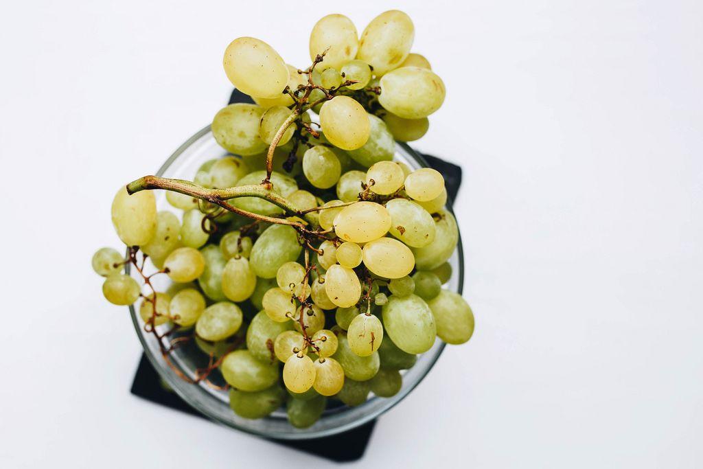 Draufsicht von Weintrauben in einer Glasschüssel vor weißem Hintergrund