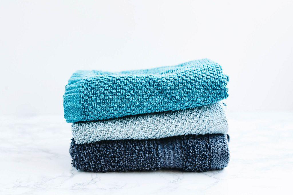 Drei Badetücher verschiedener Farben vor weißem Hintergrund