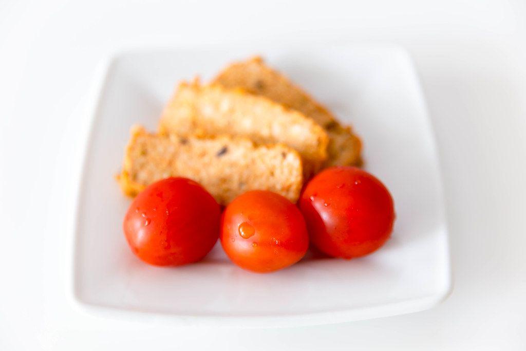 Drei gewaschene Tomaten auf einem weißen Teller, vor dem mediterranen Bio-Fleischersatz