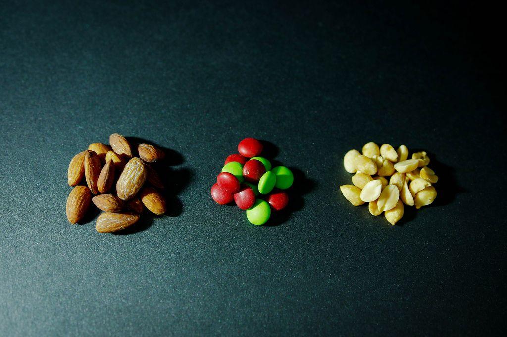 Drei Haufen mit Mandeln, bunten Süßigkeiten und geschälten Erdnüssen auf dunklem Untergrund