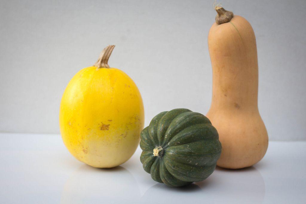 Drei Kürbisse in verschiedenen Formen, ein gelber, ein grüner und ein Brauner auf weißem Hintergrund