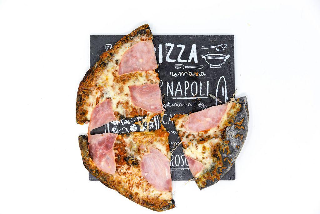 Drei Stücke der Gustavo Gusto Prosciutto-Pizza mit schwarzem Aktivkohle-Pizzaboden in der Aufsicht