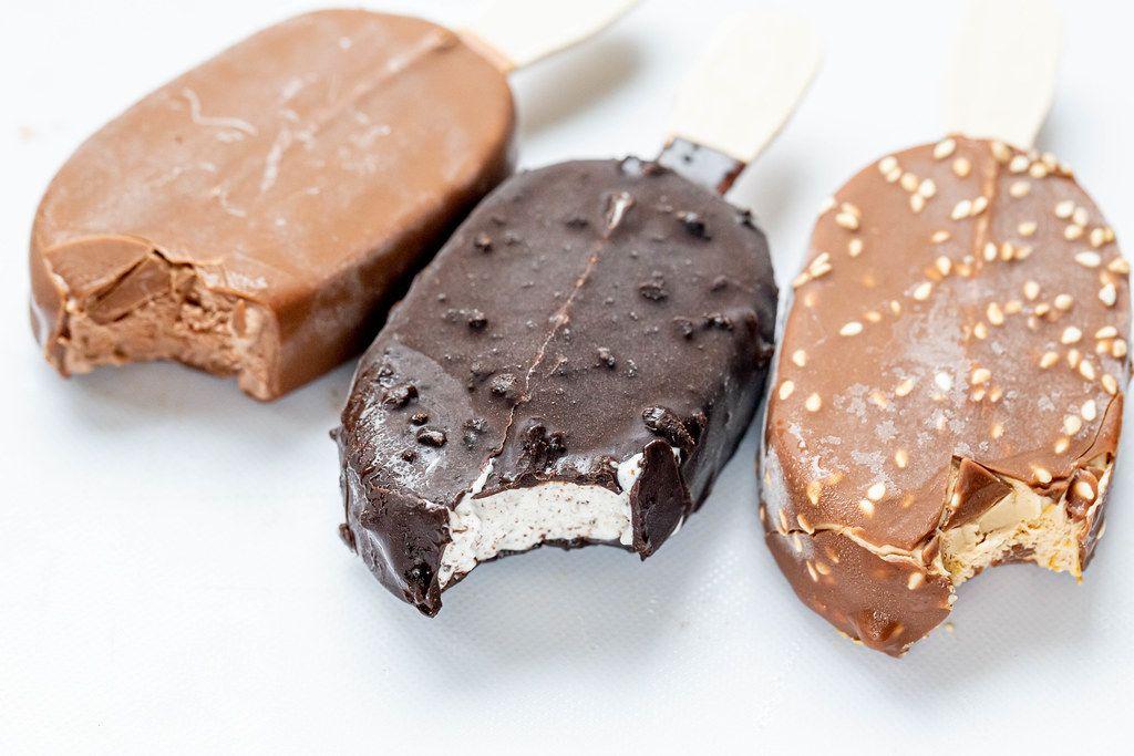 Drei verschiedene Schokoladeneis am Stiel auf weißer Oberfläche