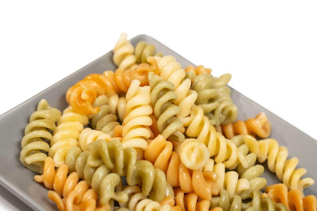 Dreifarbige, gekochte Fusilli Pasta al dente auf grauem Teller vor weißem Hintergrund