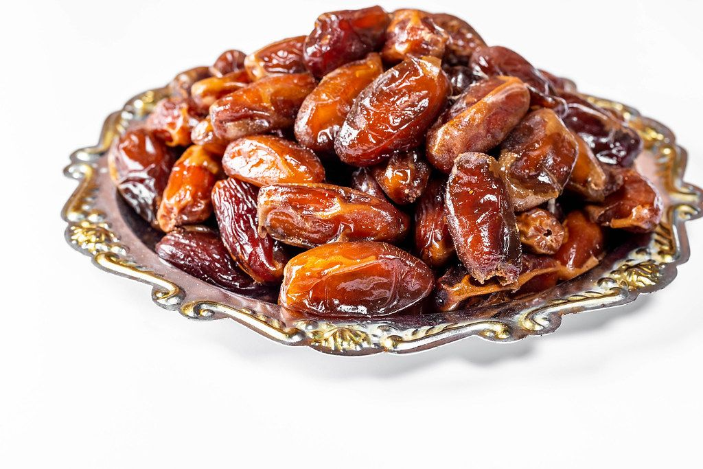 Dried dates in a vintage metal tray on white background