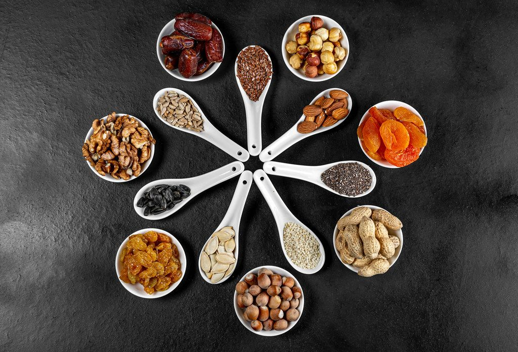 Dried fruits, nuts and seeds in spoons and bowls on a black background. Top view