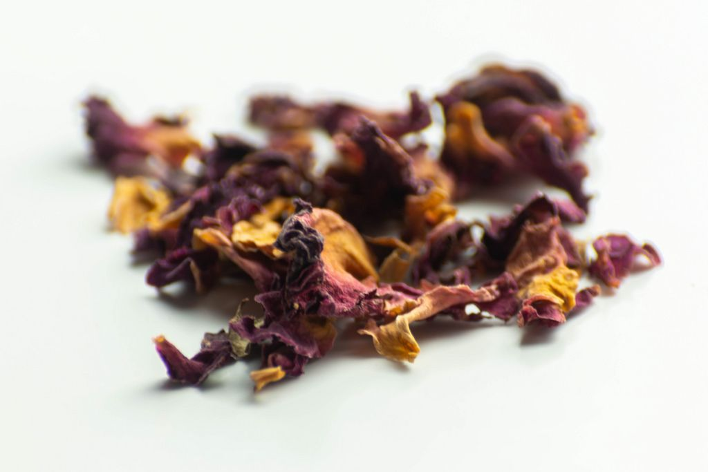 Dried pieces of rose petals scattered on a white background