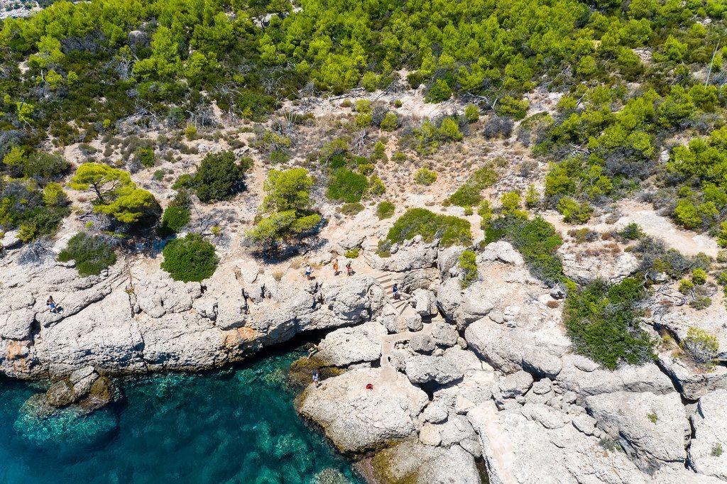 Drohnenaufnahme zeigt Touristen auf einer Gesteinsküste, beim Erkunden der Sehenswürdigkeit Bekiris Höhle, auf der saronischen Insel Spetses