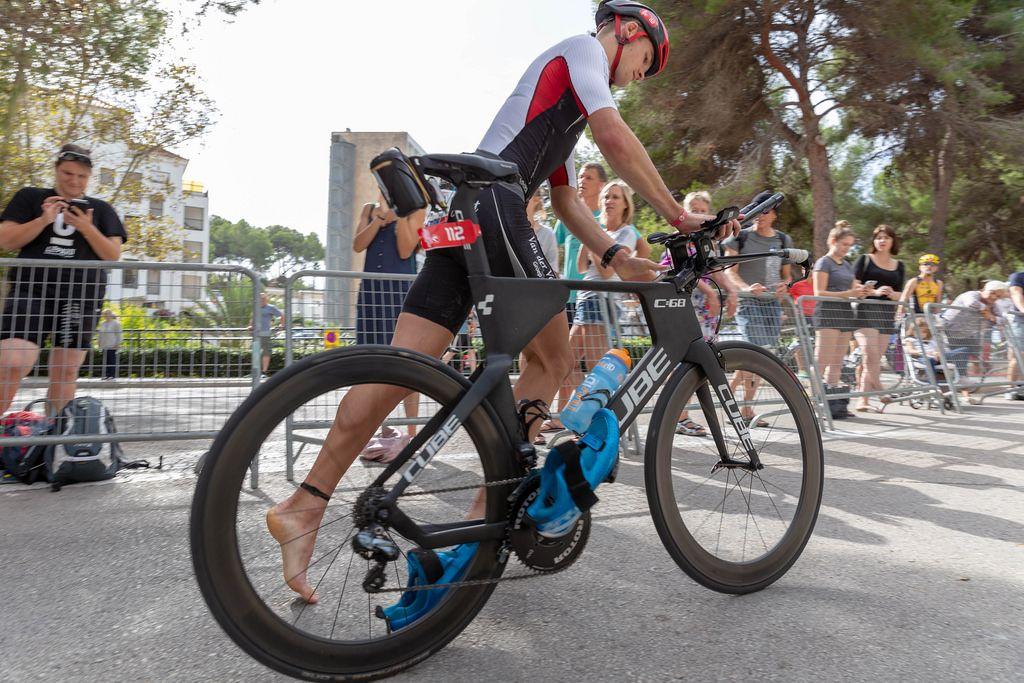 Dynamische Quersicht - Ein Sportler mit Nummer 112 besteigt sein Rad beim Challenge Triathlon in Peguera