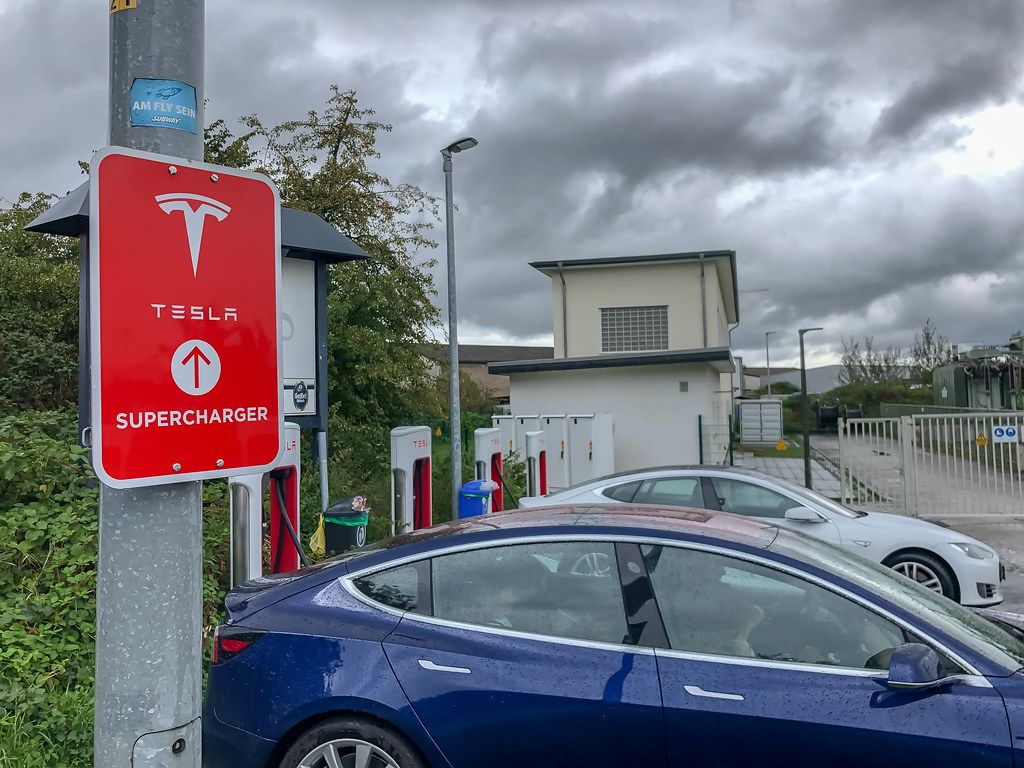 E-Cars parked at Tesla Supercharging Stations in Germany, under cloudy sky