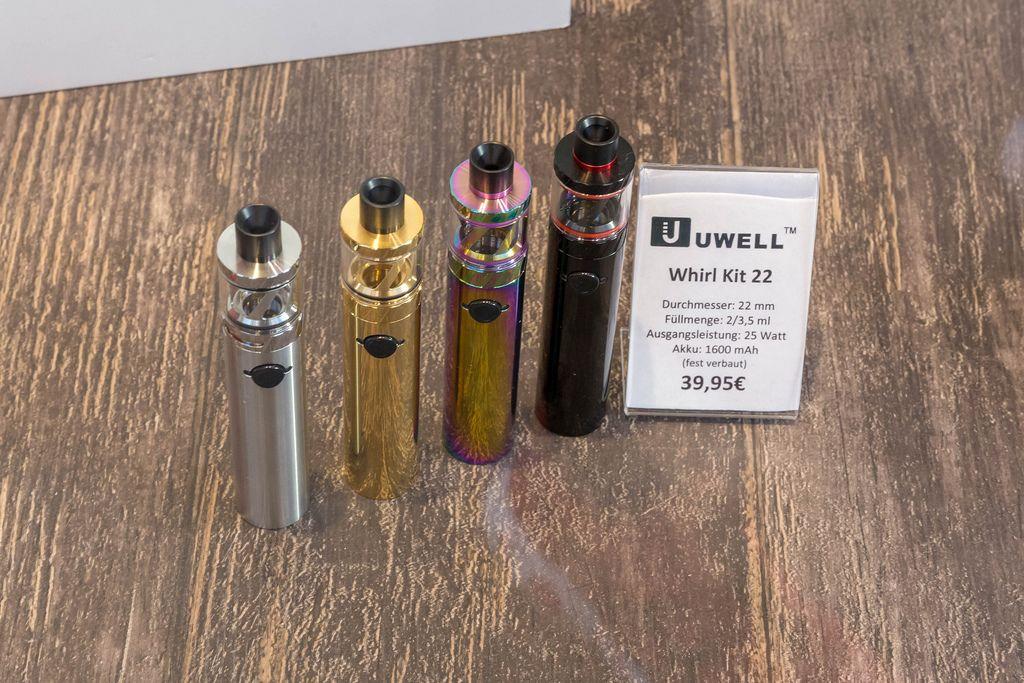 E-Zigaretten Uwell Whirl Kit 22 in silberfarben, goldfarben, regenbogenfarben und schwarz auf Holztisch