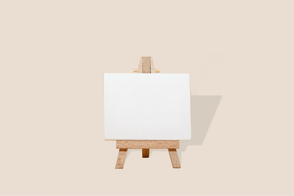 Easel with blank canvas on cream background