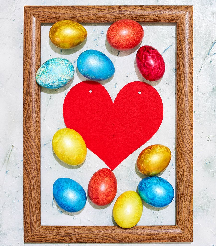 Easter concept. Colorful easter eggs placed in the wooden picture frame