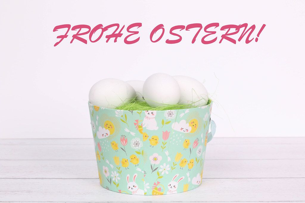 Easter eggs in a basket and Frohe Ostern text