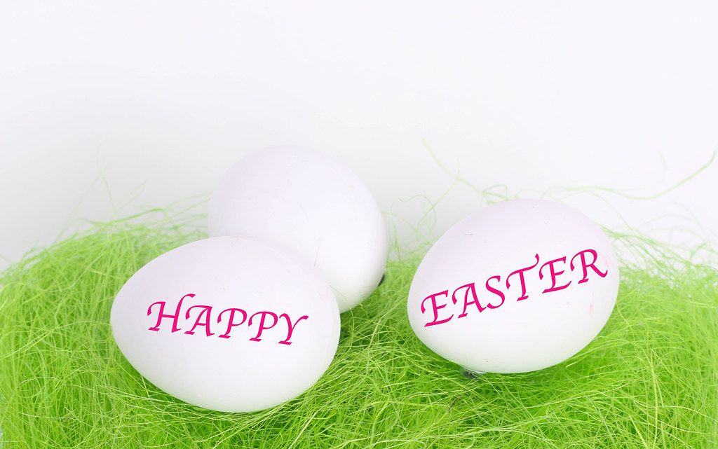 Easter eggs on green grass with Happy Easter text