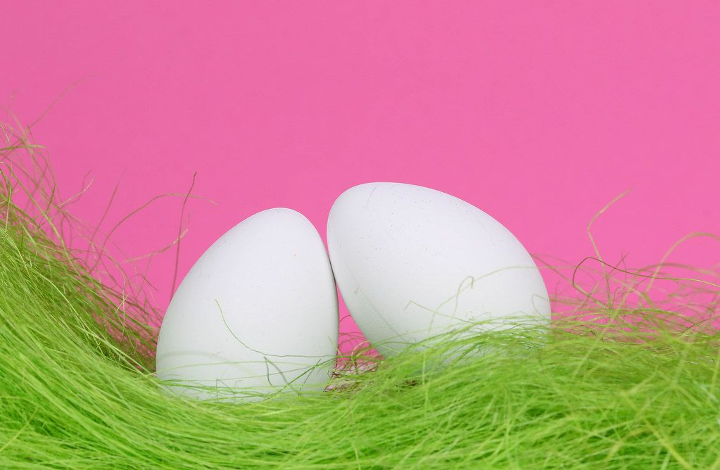 Easter eggs with green grass and pink background