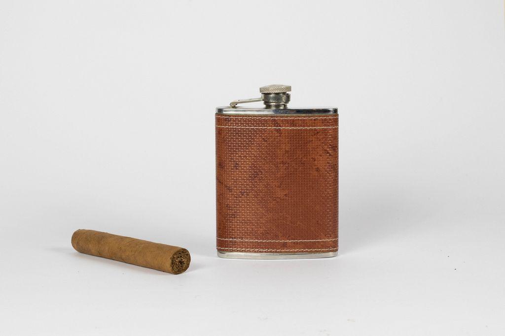 Edelstahl Flachmann in Leder und Zigarre auf weißem Hintergrund