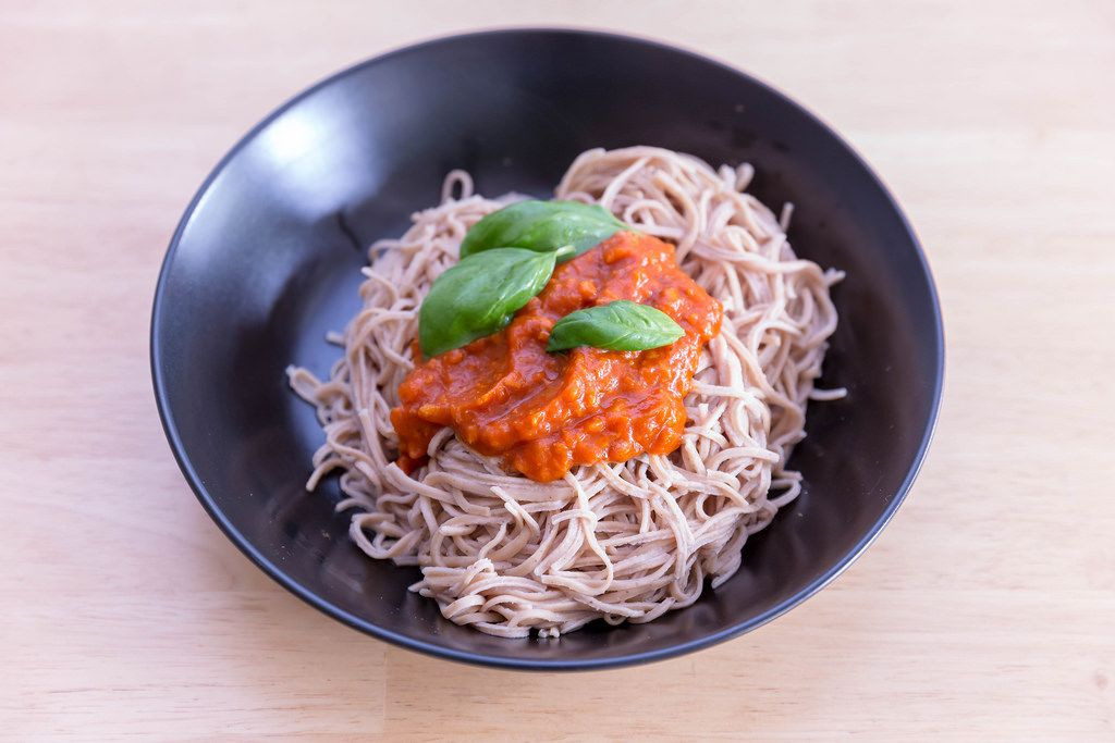 Edemama Bio-Spaghetti made from azuki beans with tomatosauce and basil leaves on a black plate