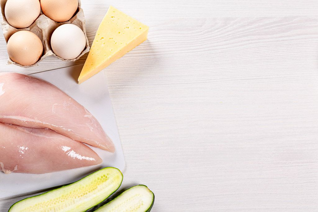 Eggs, cheese, raw chicken breast and cucumber on white wooden background