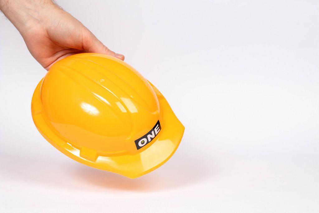 Ein Arbeiter hält einen Schutzhelm auf weißem Hintergrund