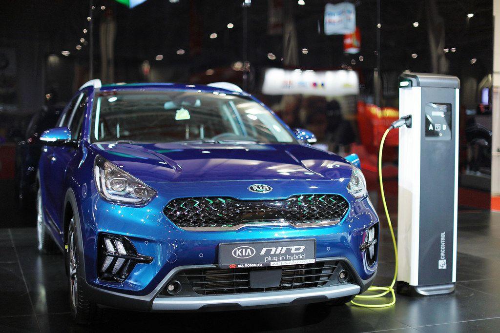 Ein blaues KIA Niro Plug-In Hybrid wird bei einer Ladestation auf der Automesse in Bukarest geladen