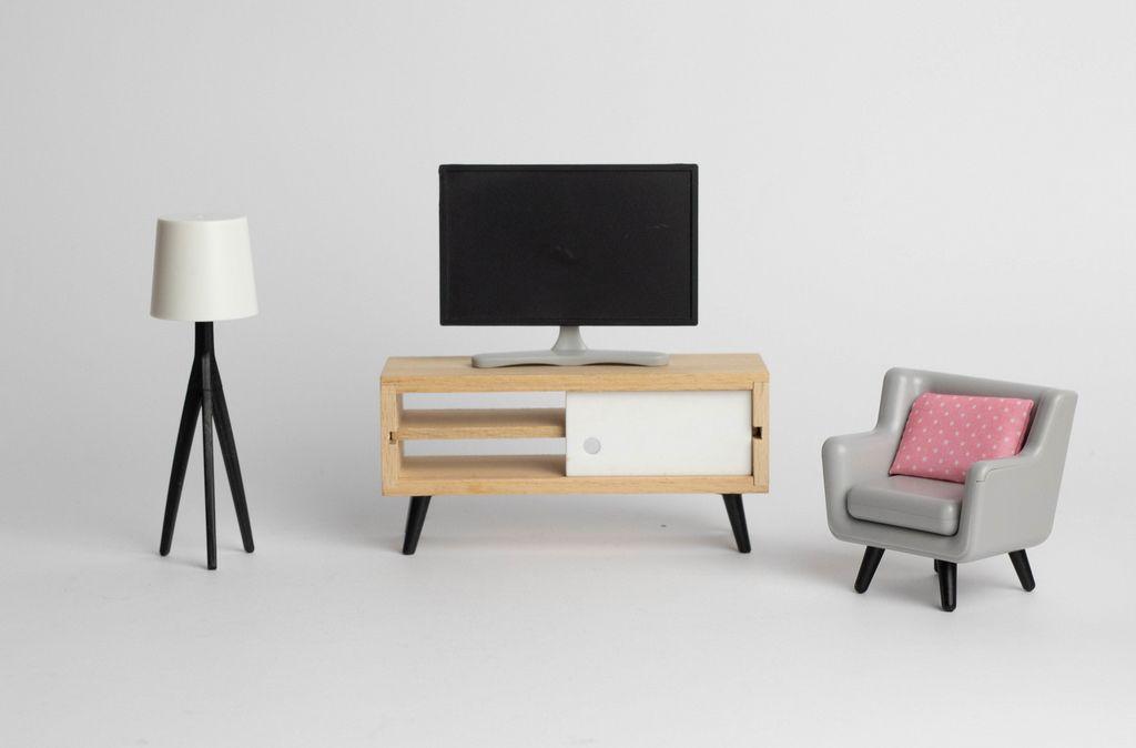 Ein Fernsehertisch zwischen einer Lampe und einem Sessel