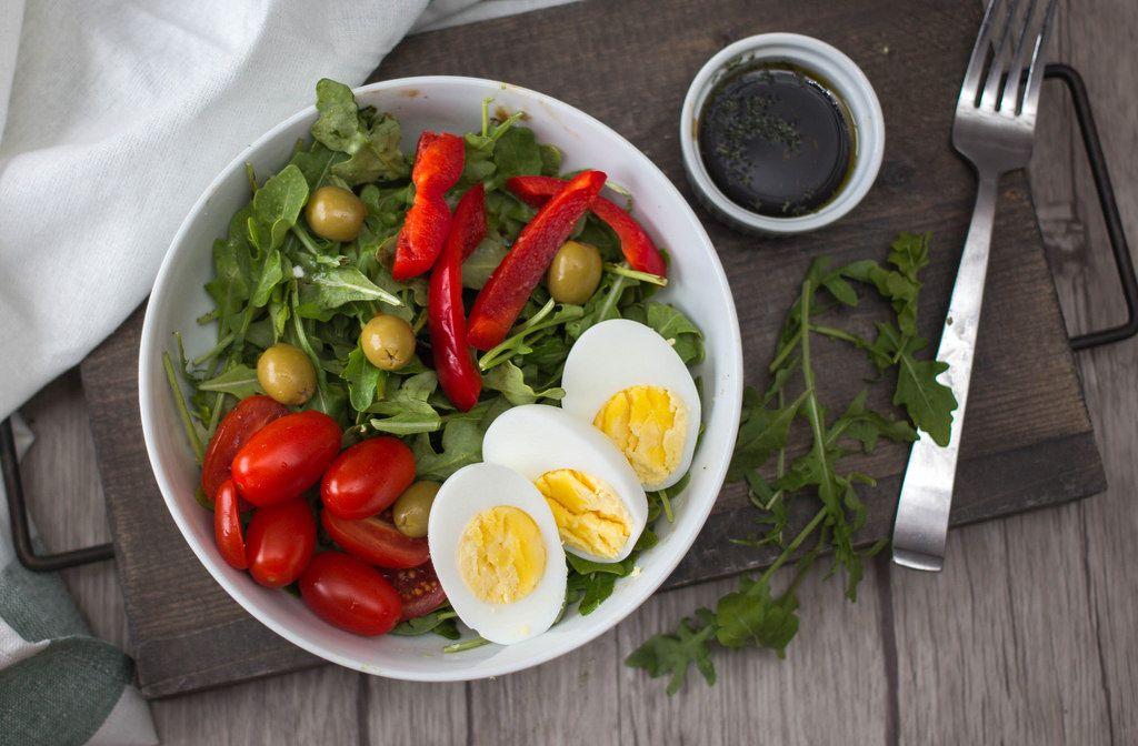 Ein frischer Salat aus Rucola, Oliven, Paprika und Kirschtomaten mit Ei in einer weißen Schüssel in der Aufsicht