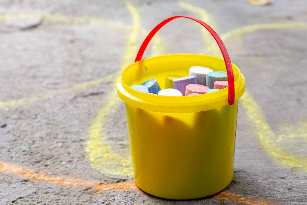 Ein gelber Eimer mit Kreide, für Kinder-Straßenmalereien