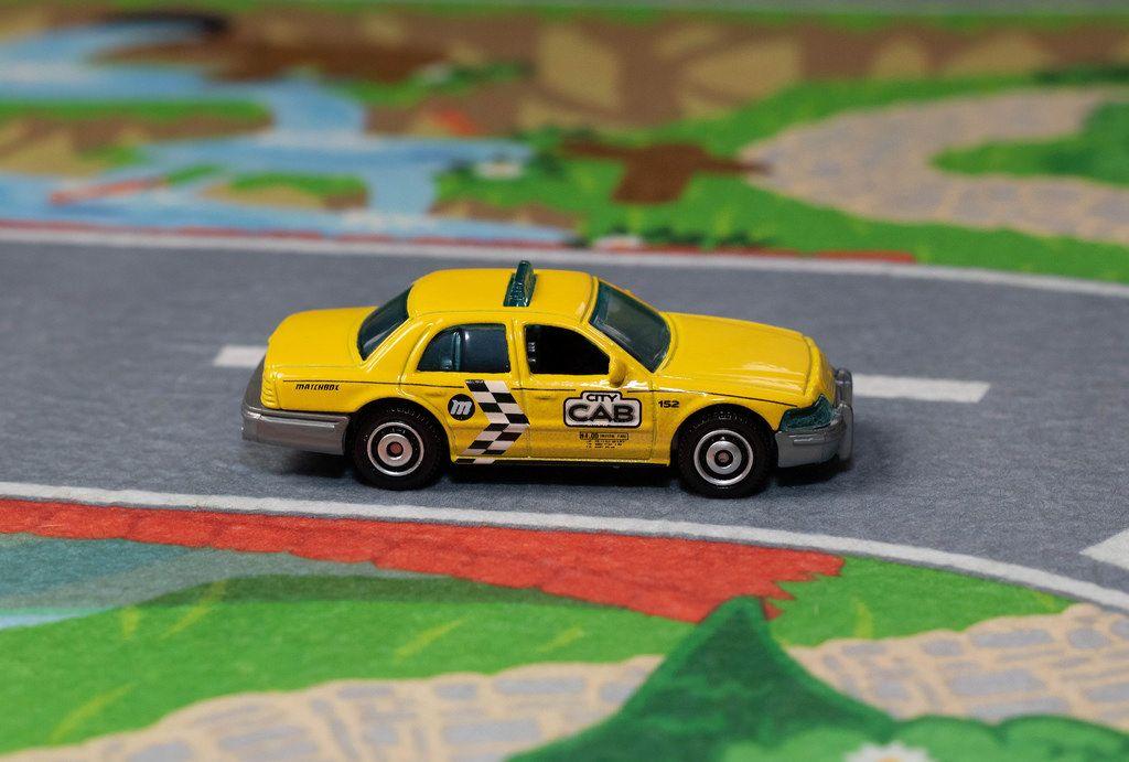 Ein gelbes Taxi fährt auf der Straße - Modelauto