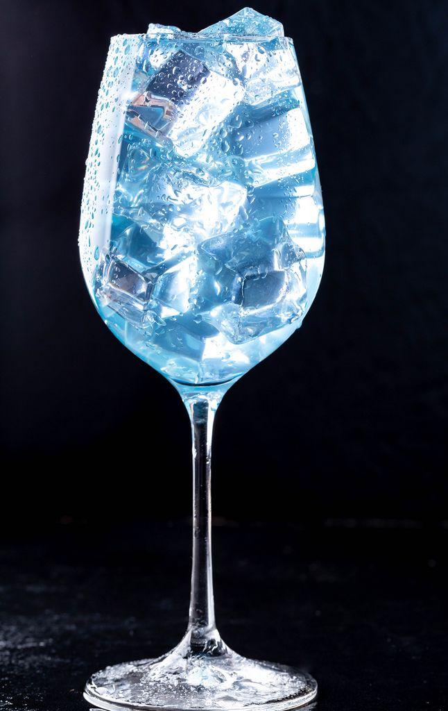 Ein Glas gefüllt mit einem blauen Cocktail und Eiswürfeln vor dunklem Hintergrund