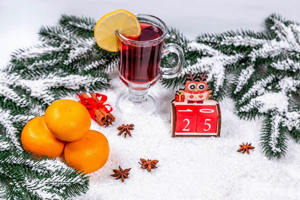Ein Glas Glühwein zwischen Tannenzweigen, Orangen, Zimt im Schnee