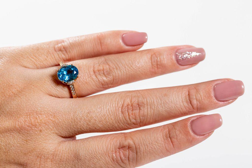 Ein goldener Ring mit einem blauem Topaz an der Hand einer Frau