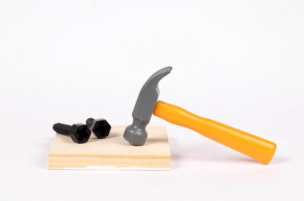 Ein Hammer und Schrauben auf einem Brett - Plastik Werkzeug