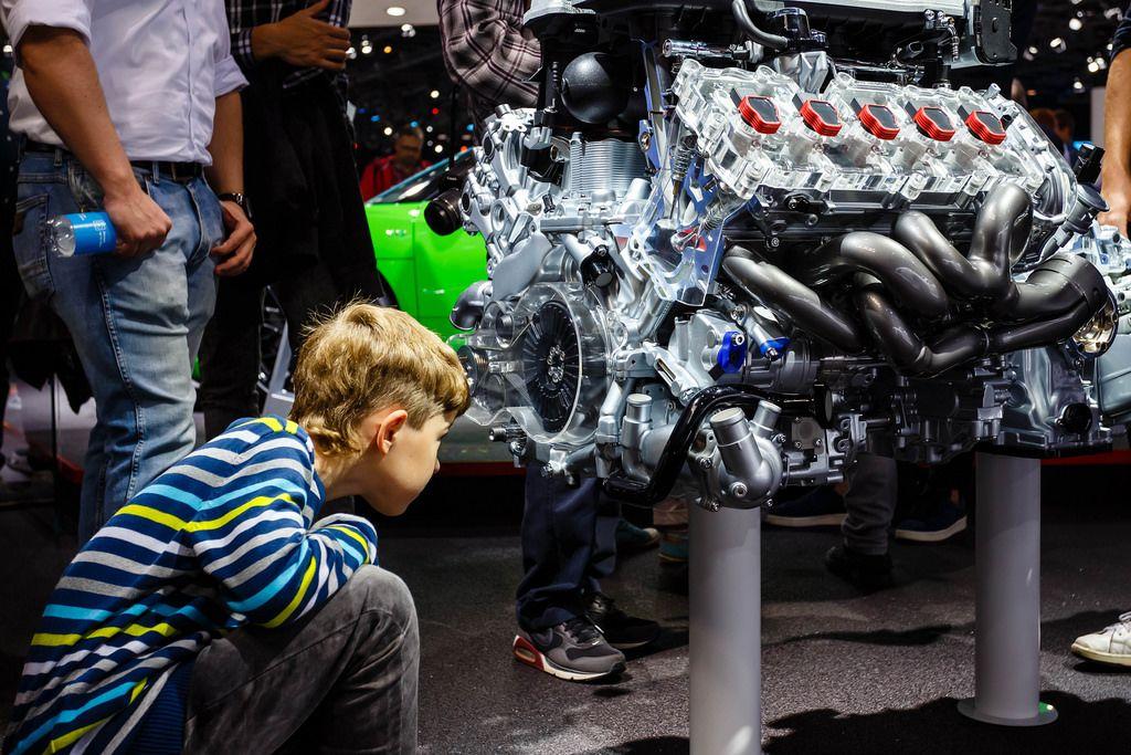 Ein Junge schaut in das Innere des Motors vom Audi R8 V10 plus