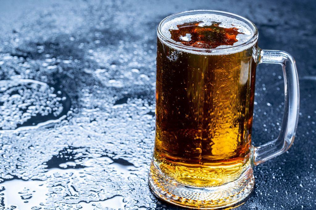 Ein Krug mit frischem Bier auf dunklem Hintergrund