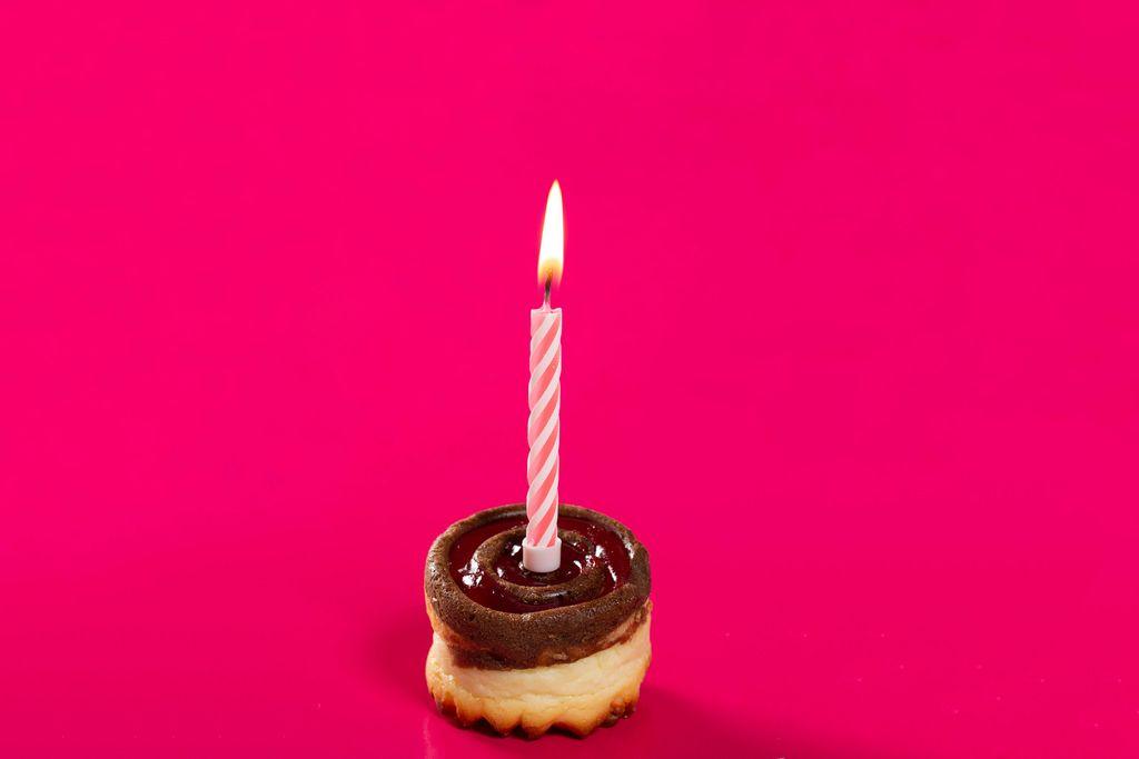Ein Küchlein mit angezündeter Kerze auf pinkem Hintergrund