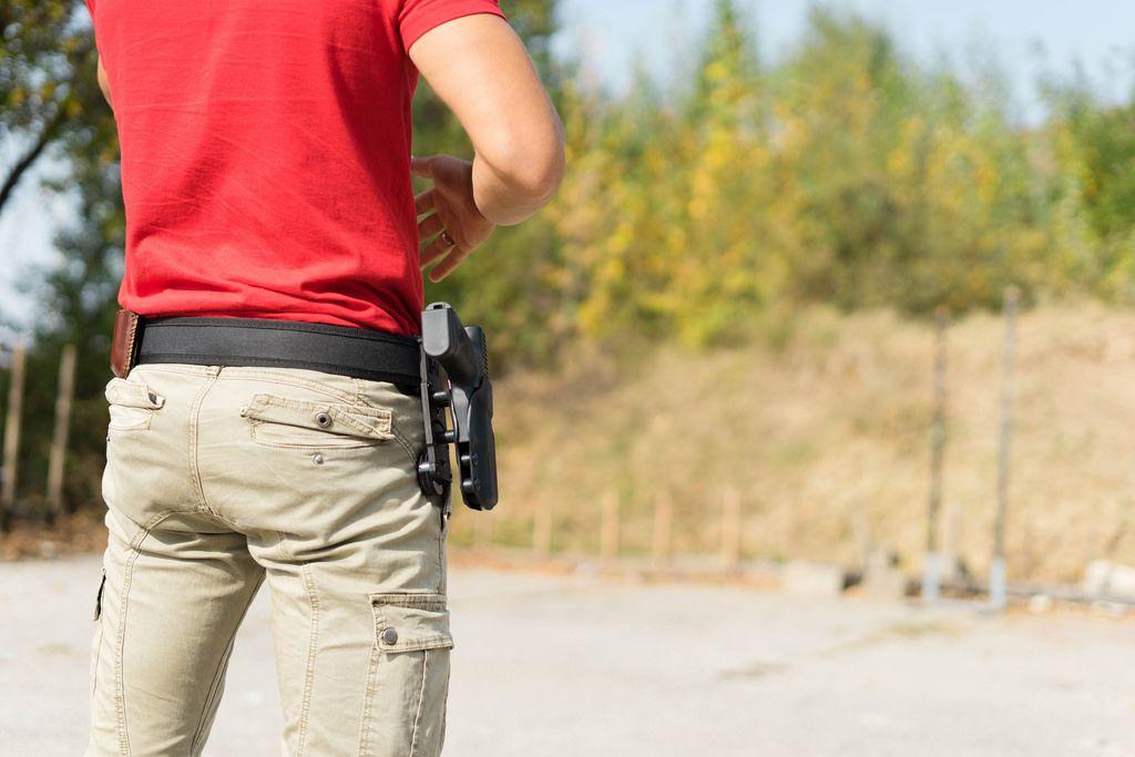 Ein Mann an graift nach seiner Pistole im Holster
