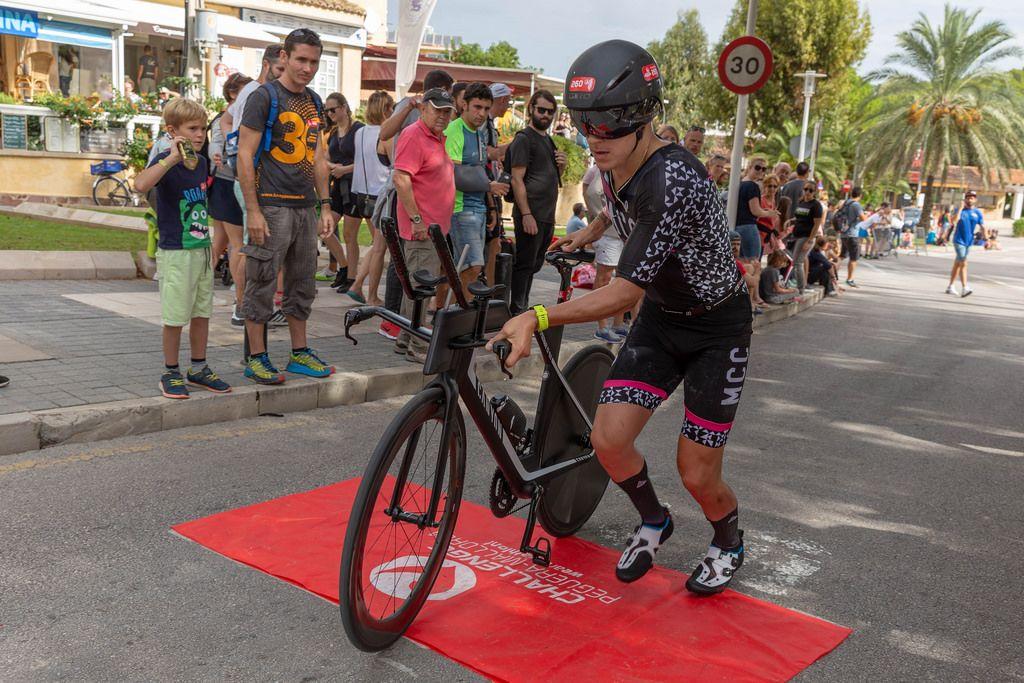 Ein Mann bei einem Triathlon wechselt von Lauf auf Radfahren