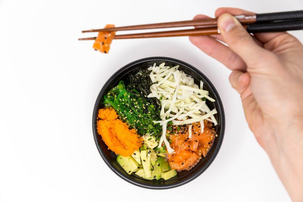 Ein Mann entnimmt mit Essstäbchen ein Stück Lachs aus der Poke Teriyaki Lachs Bowl
